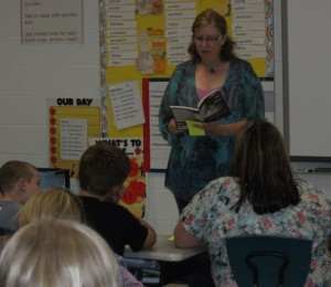 Cathy reads to a class of fifth grade students as part of a school visit